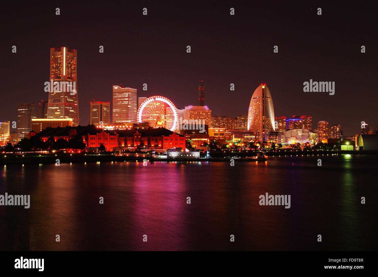 River In Front Of Illuminated Cityscape Against Sky At Night - Stock Image