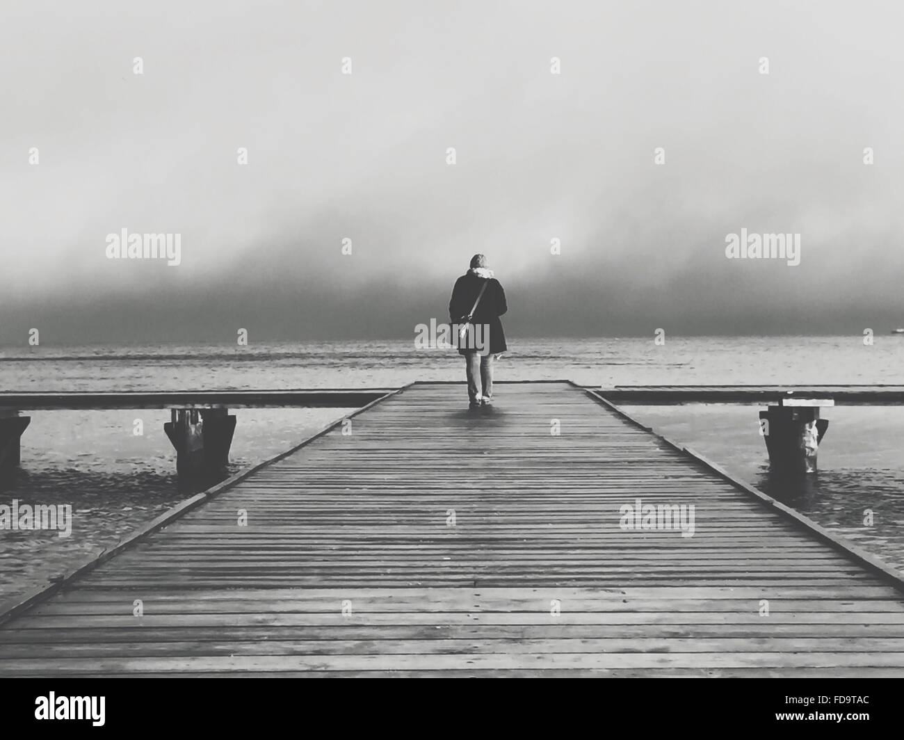 Full Length Rear View Of Woman Walking On Pier - Stock Image