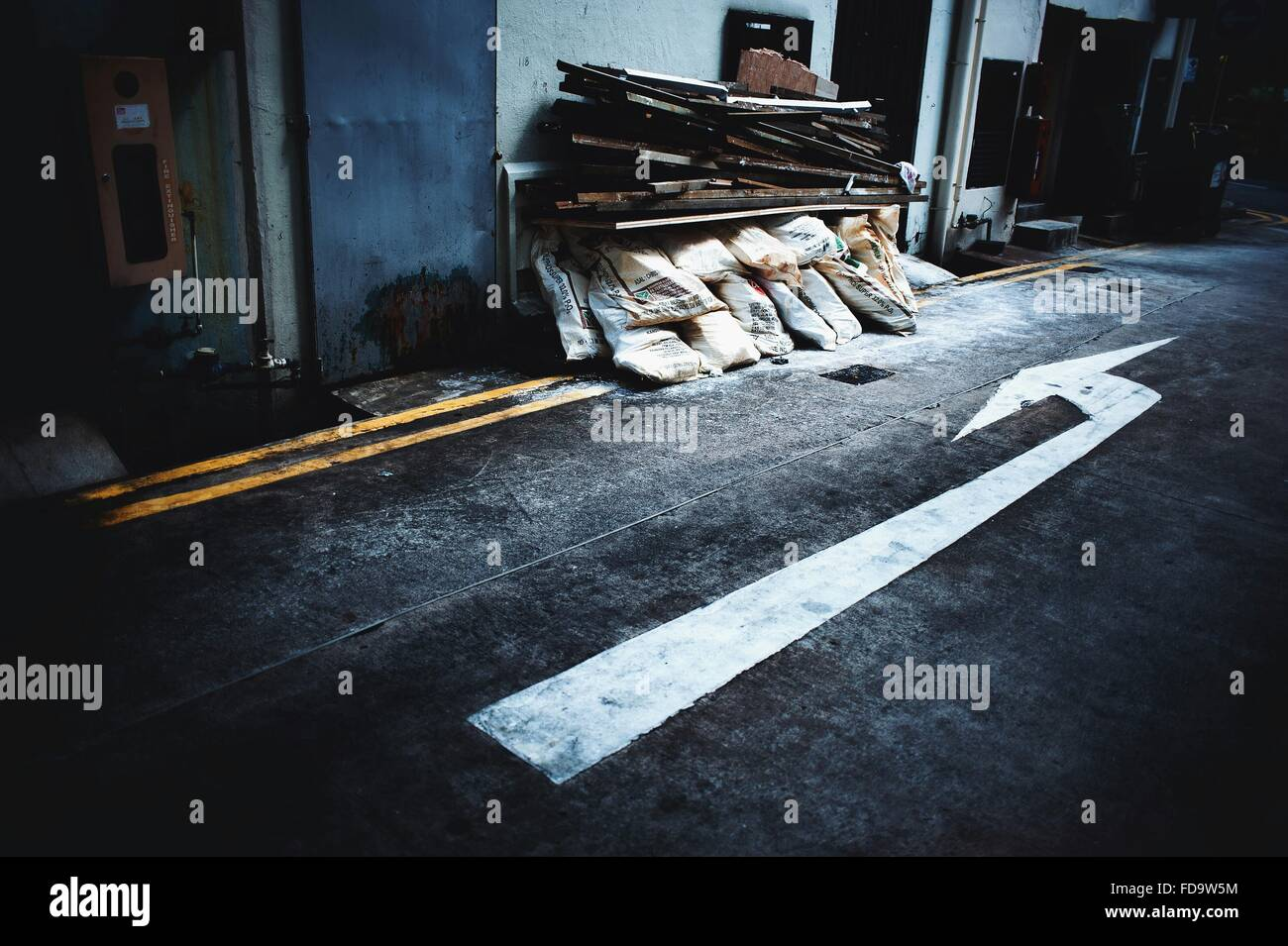 Arrow Sign On Road Pointing At Stack Of Sacks - Stock Image