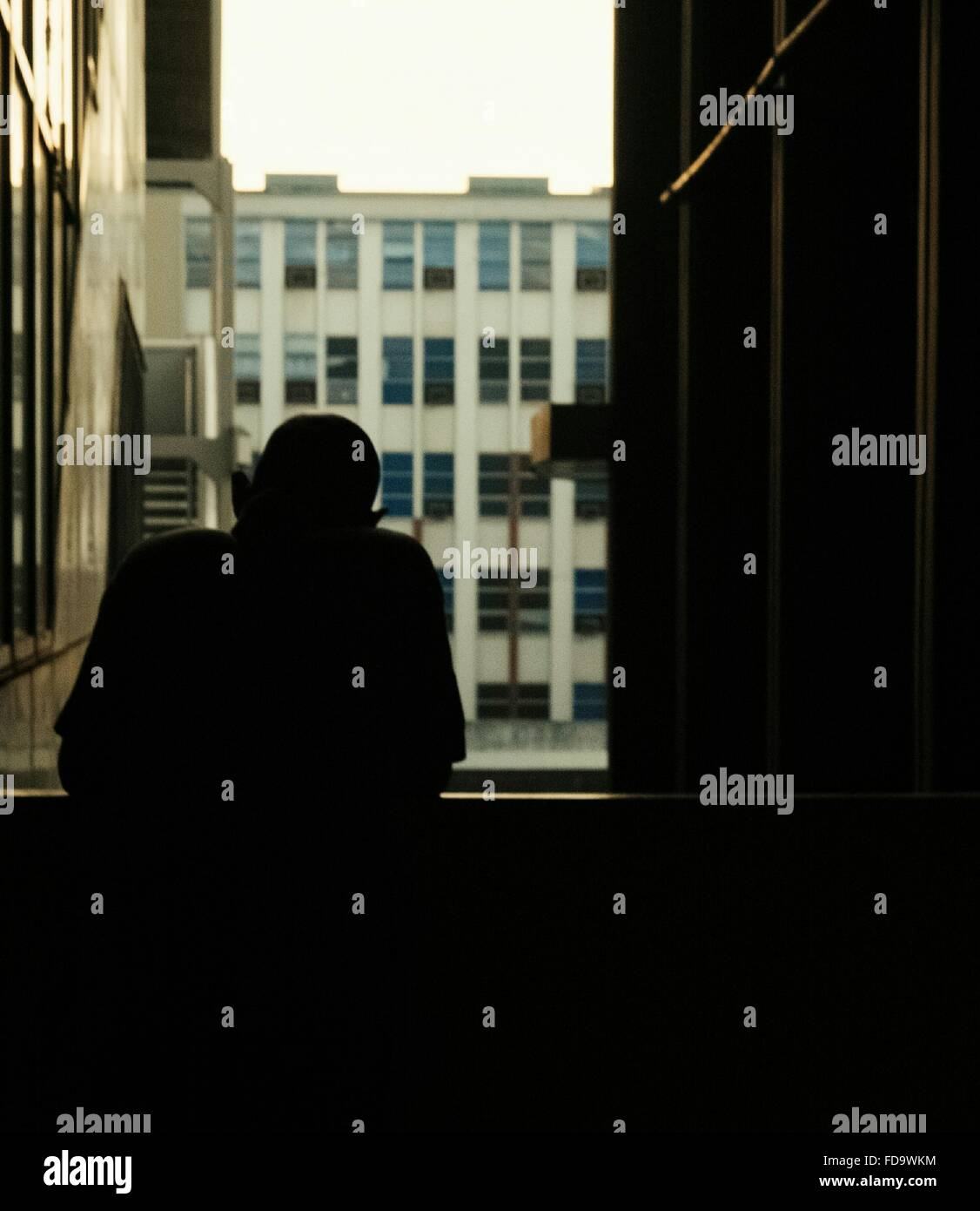 Silhouette Of Man Looking Through Window - Stock Image