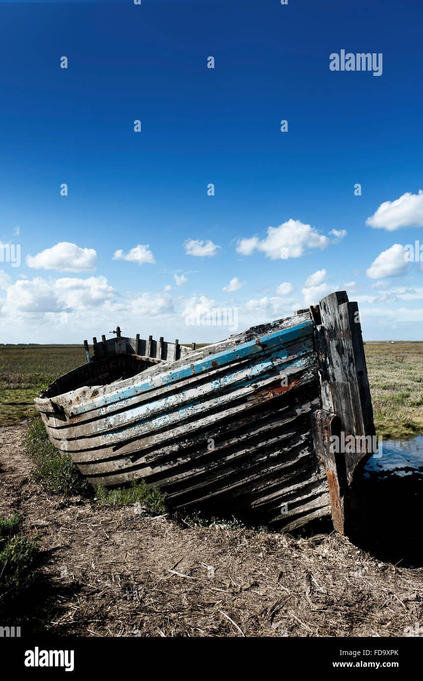 Wooden rowing boat with peeling paint on coastal headland, Norfolk, England, UK - Stock Image