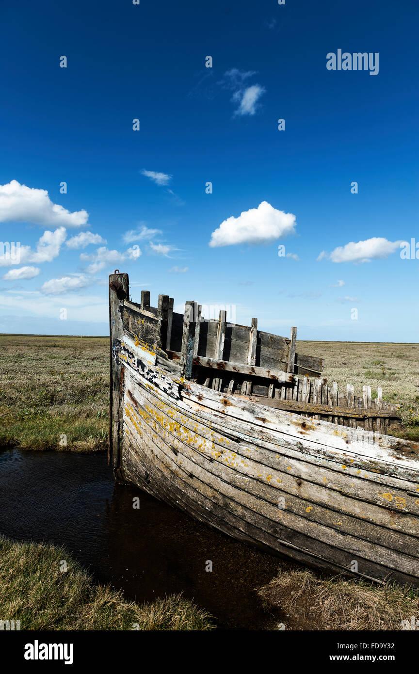 Abandoned rowing boat in coastal Norfolk, England, UK - Stock Image