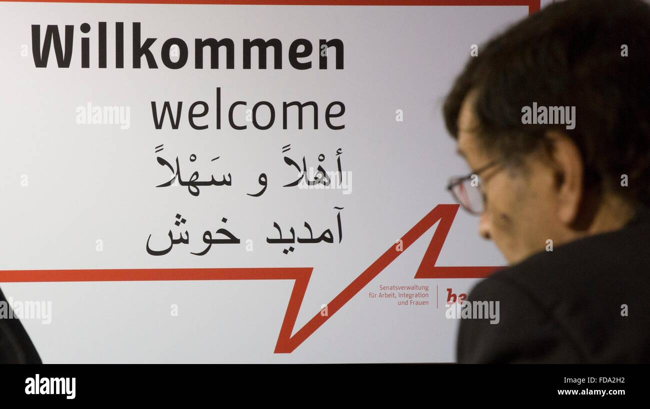 A journalist looks at a sign with 'Welcome' written in German, English and Arabic at a new job center for migrants Stock Photo