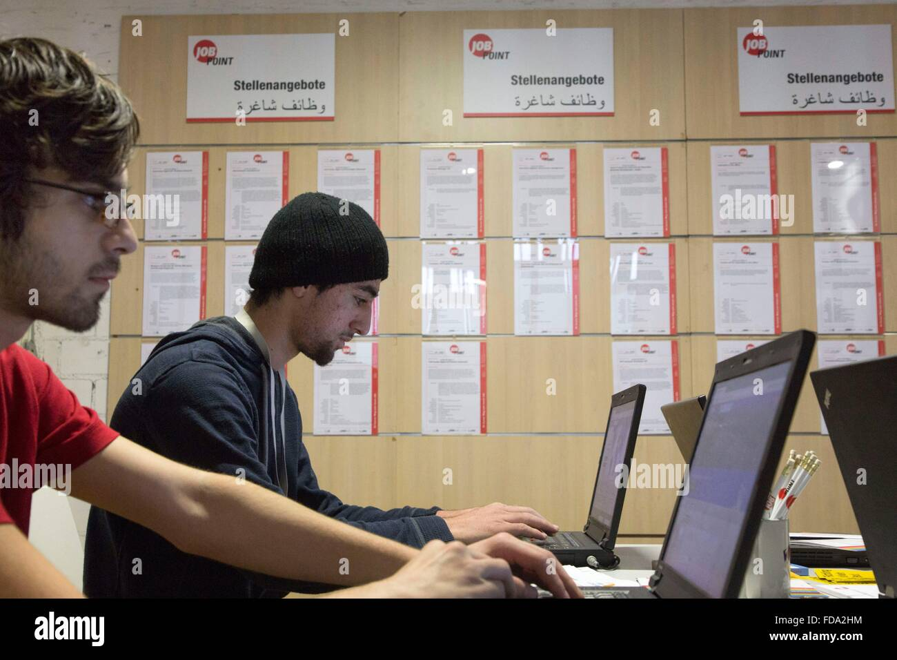 Refugees from Syria look at job offers at a new job center for migrants and refugees at former Tempelhof Airport Stock Photo