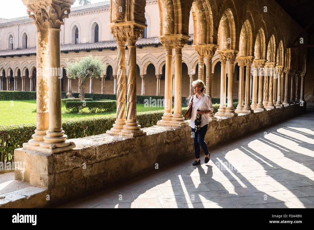 Woman walking in the cloisters of Monreale Cathedral  in the province of Palermo, Sicily - Stock Image