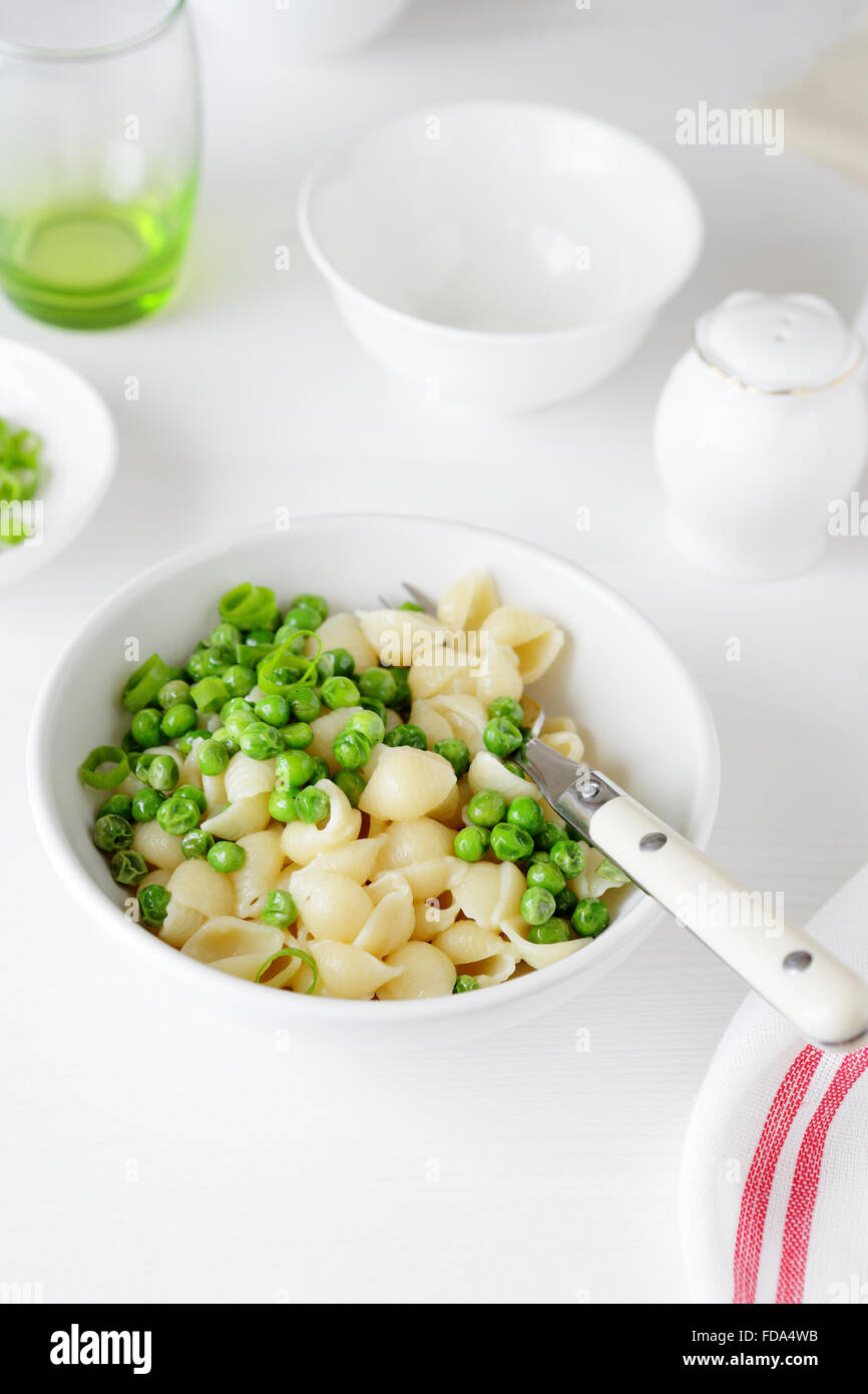 pasta with green peas in white bowl, fod close-up - Stock Image