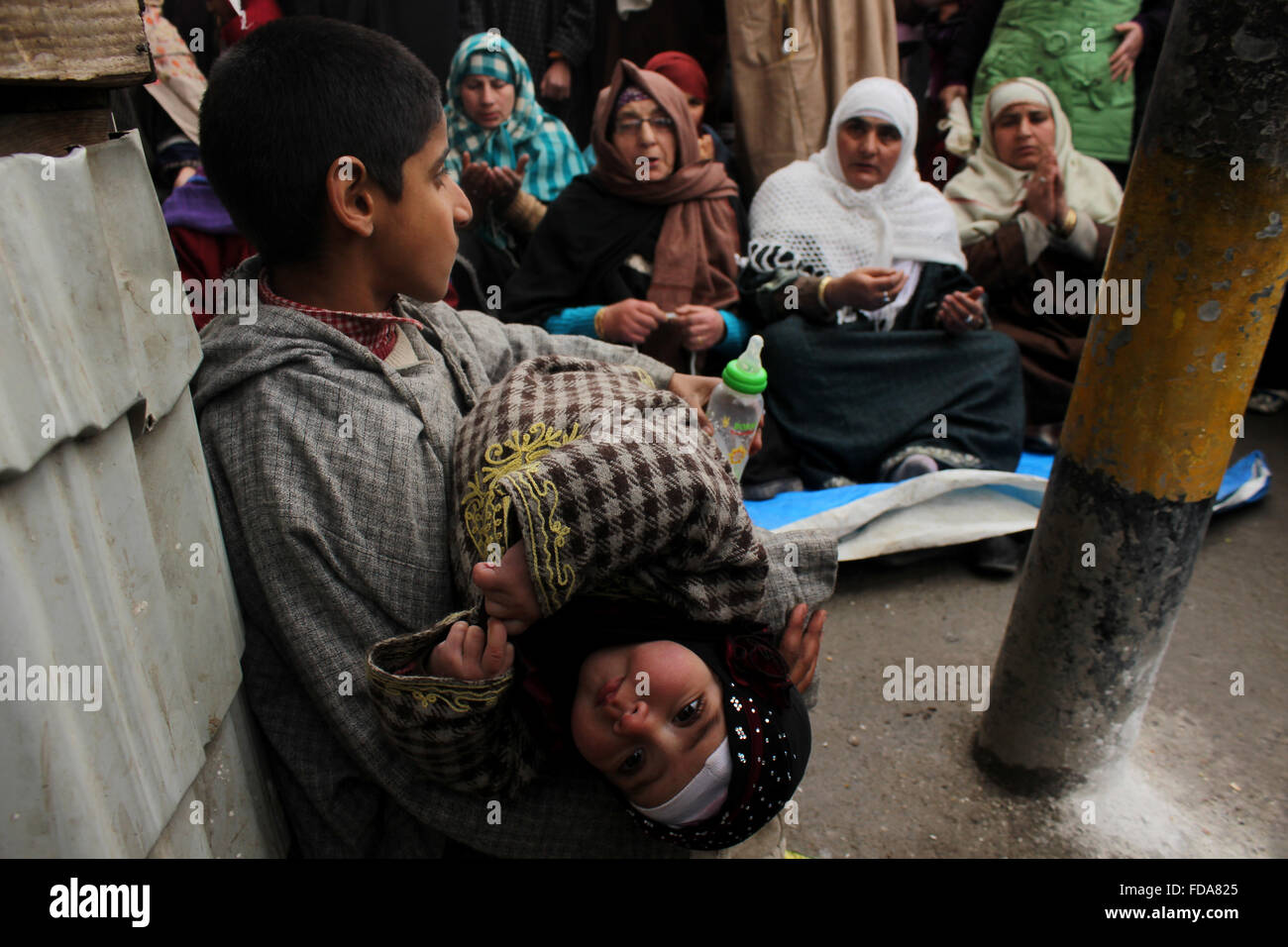 A kashmiri Muslim boy feeding her sister in lap as their mother is offering prayers at the holy shrine of a famous - Stock Image