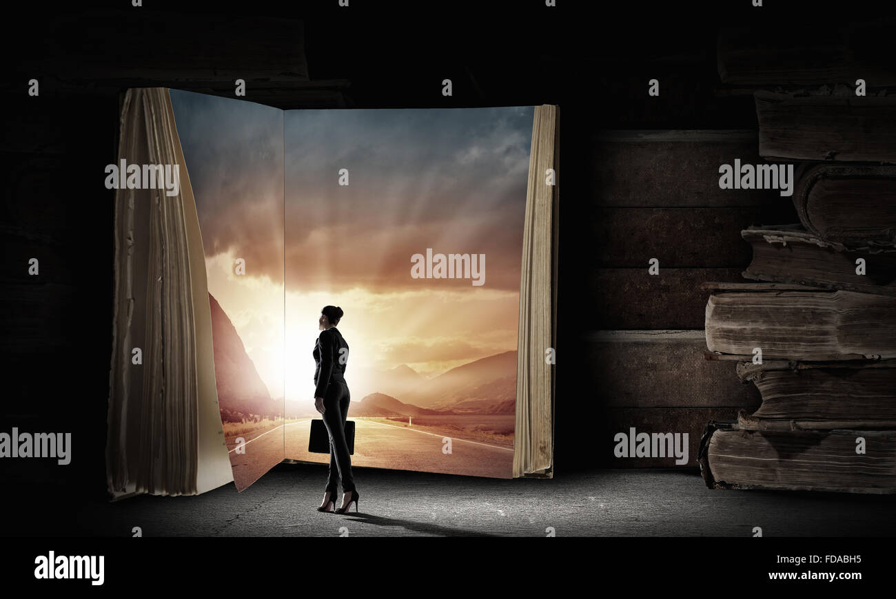 Big old opened book and miniature of businesswoman - Stock Image