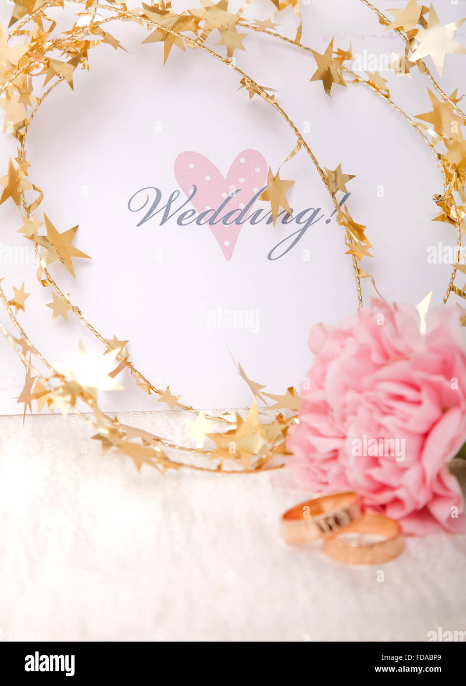 Wedding invitation with gold ribbon and rings - Stock Image