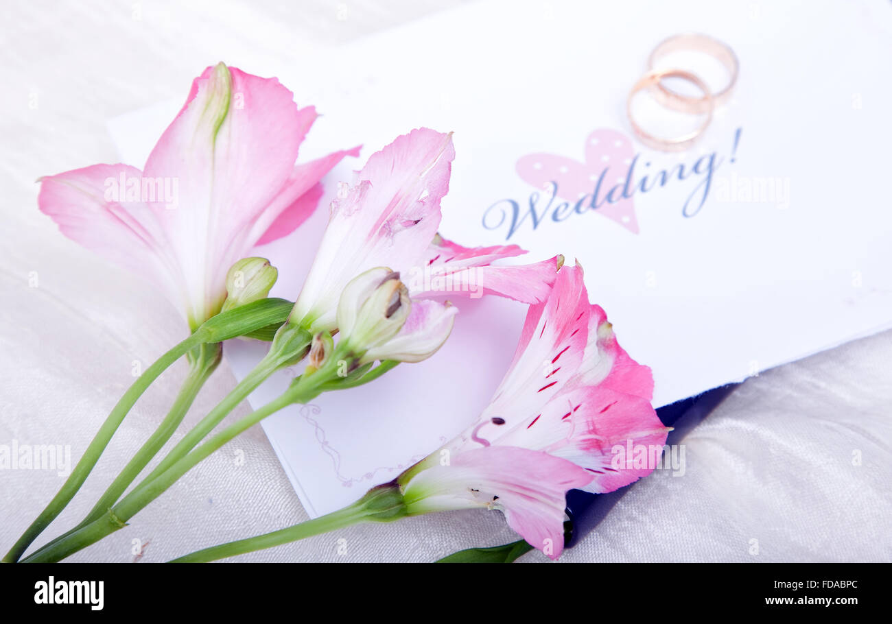 Beautiful pink lilies rest on top of a wedding invitation with the wedding rings out of focus in the background. - Stock Image