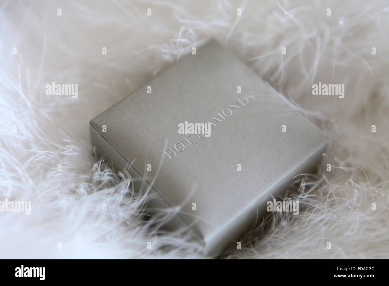 Diamond ring in a silver box on white feathers - Stock Image