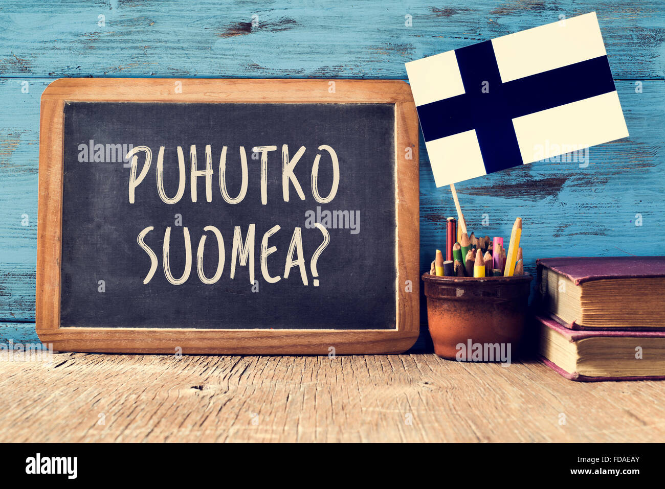 a chalkboard with the question puhutko suomea, do you speak Finnish? written in Finnish, a pot with pencils, some - Stock Image