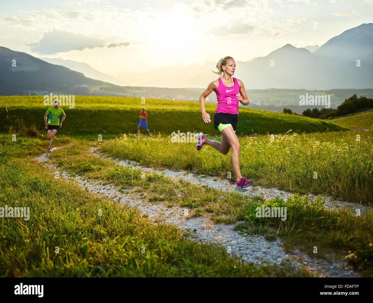 Young woman in her twenties running on path through fields, more runners behind, Rosengarten, Patsch, Tyrol, Austria - Stock Image