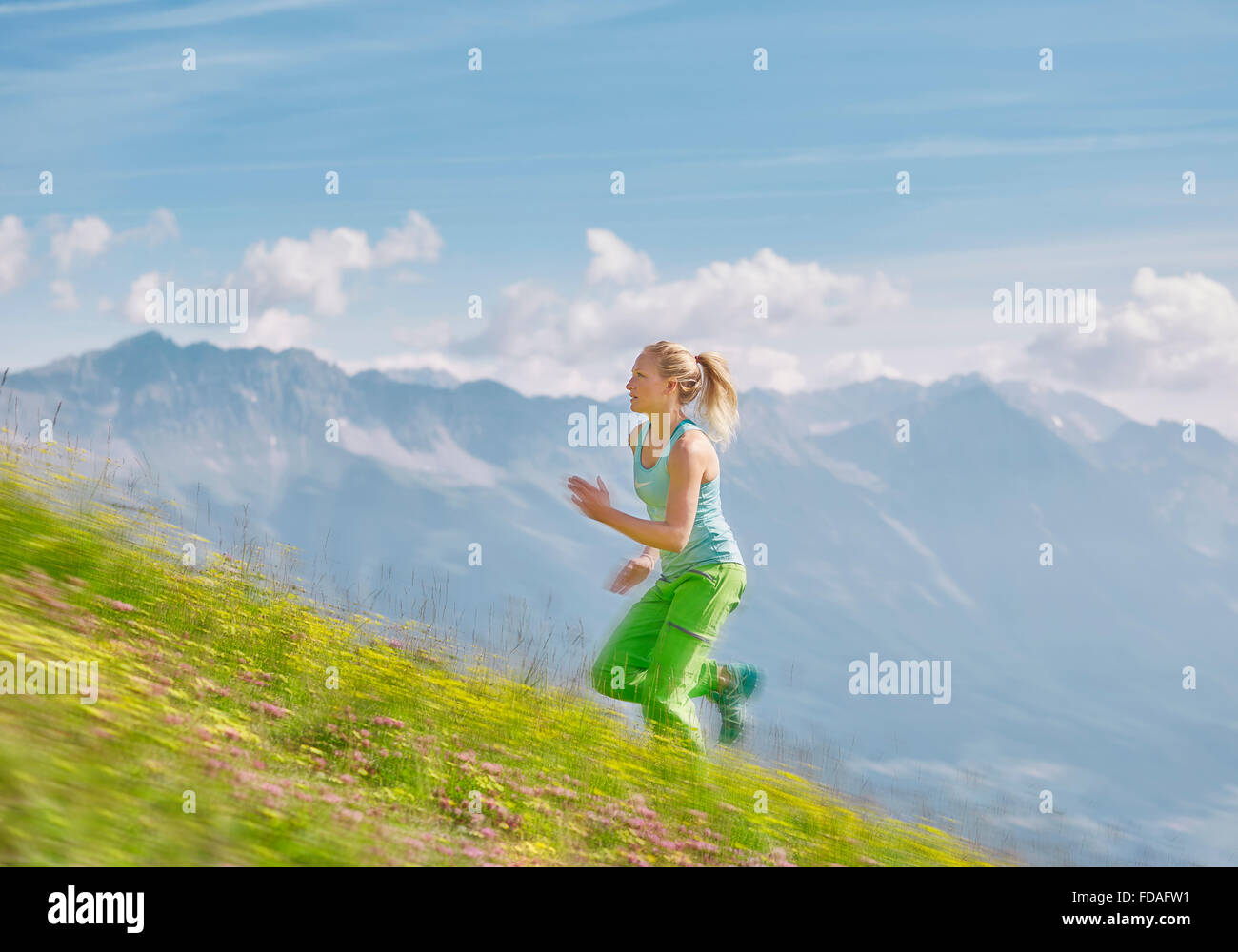 Young woman in her twenties running up field in mountains, Mutterer Alm, Innsbruck, Tyrol, Austria - Stock Image