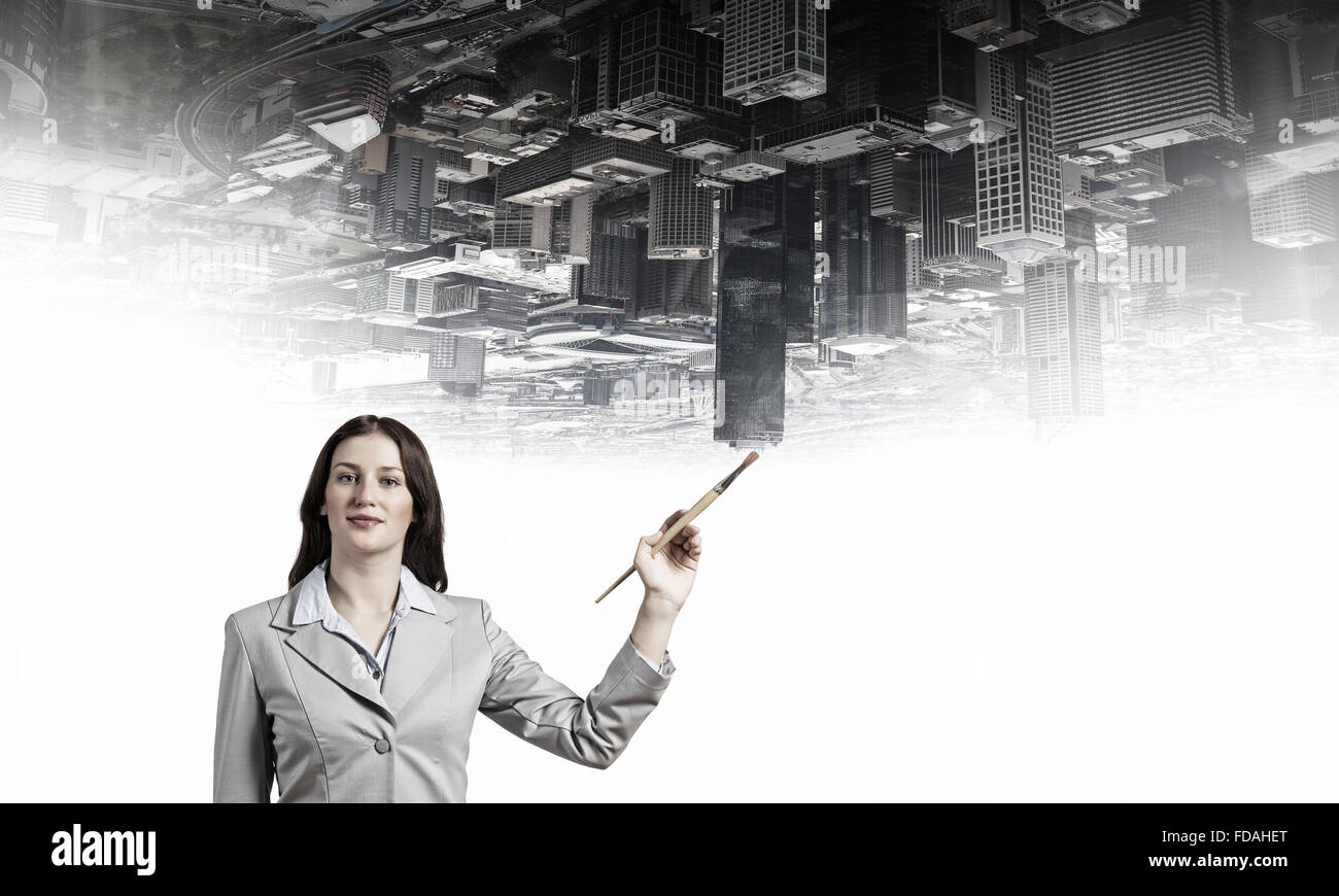 Young pretty businesswoman holding paint brush. Creativity concept - Stock Image