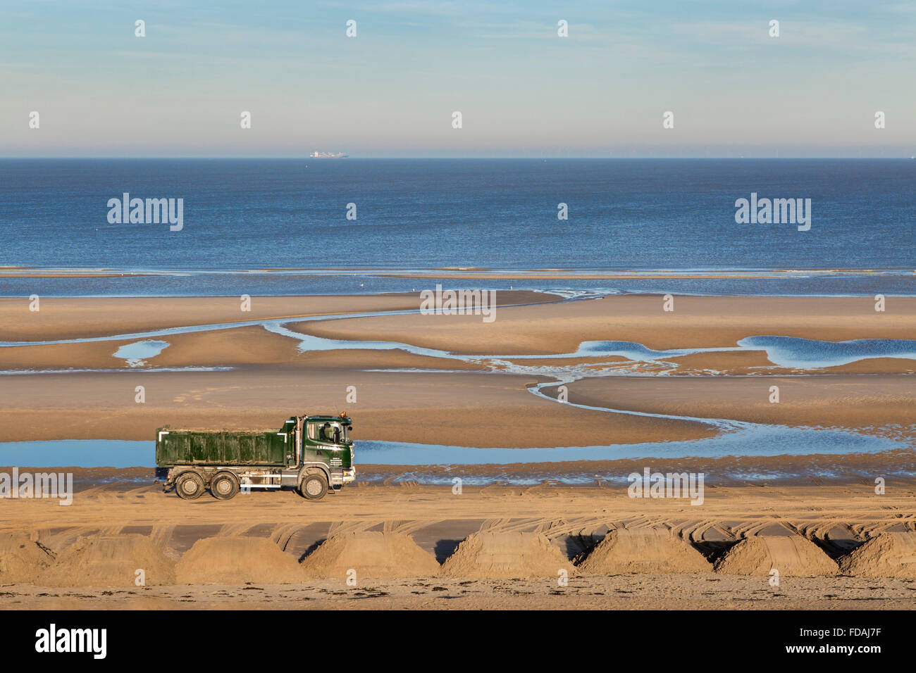 Truck at work to raise the beach along the North Sea coast at Blankenberge, Belgium - Stock Image