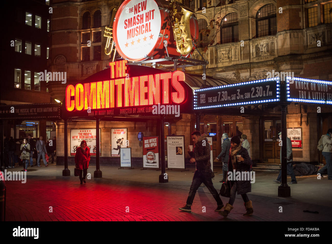 Pedestrians under neon lights of 'The Commitments' musical in Soho, London - Stock Image