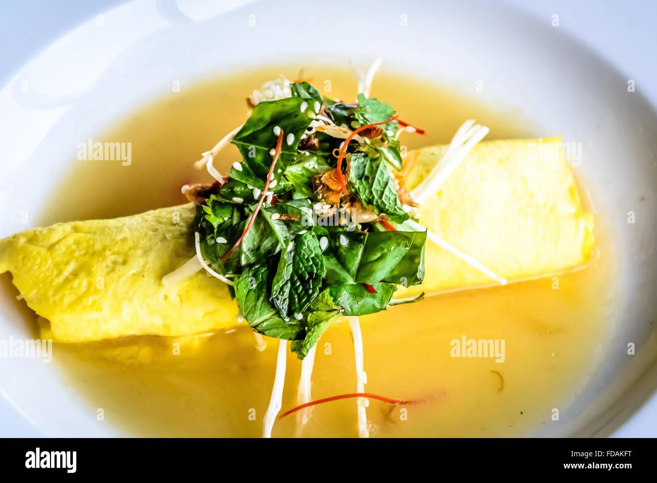 Sydney Crab Omelette, Enoki Mushroom, and Herb Salad, Miso Mustard Broth - Stock Image