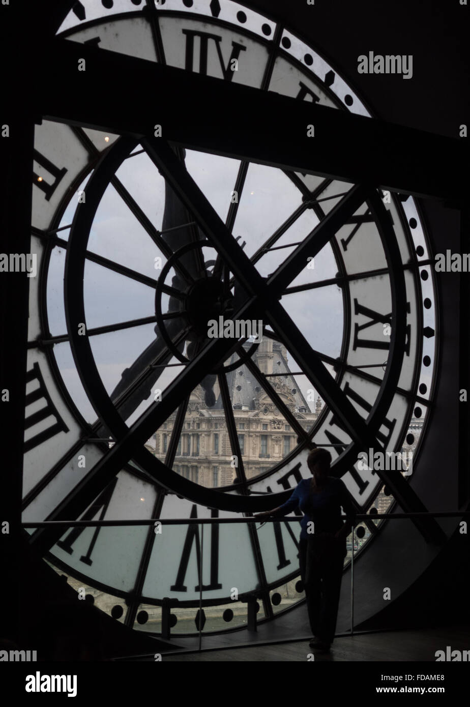 a silhouette figure standing looking through a huge clock face window onto the Paris scene outside, Musee D'Orsay - Stock Image