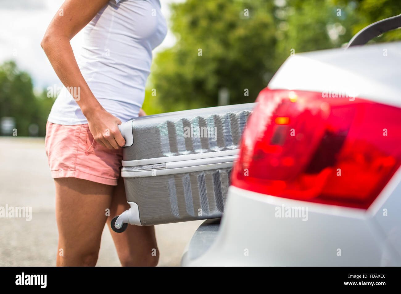 Young woman putting a have suitcase into her car's trunk - Stock Image