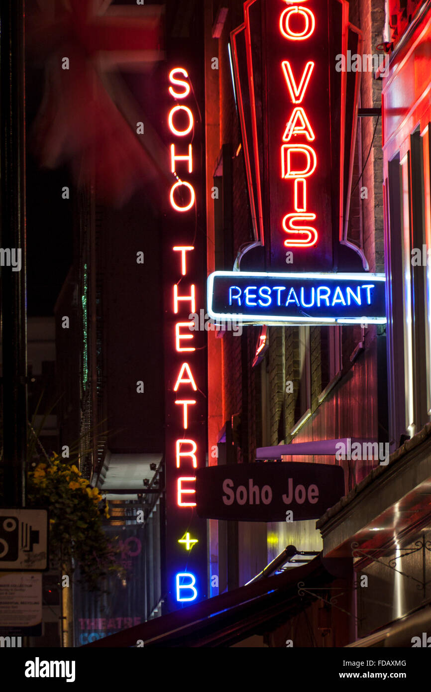 Soho Theatre neon sign at night with other signage Soho street scene nightlife Dean Street Soho London England UK - Stock Image