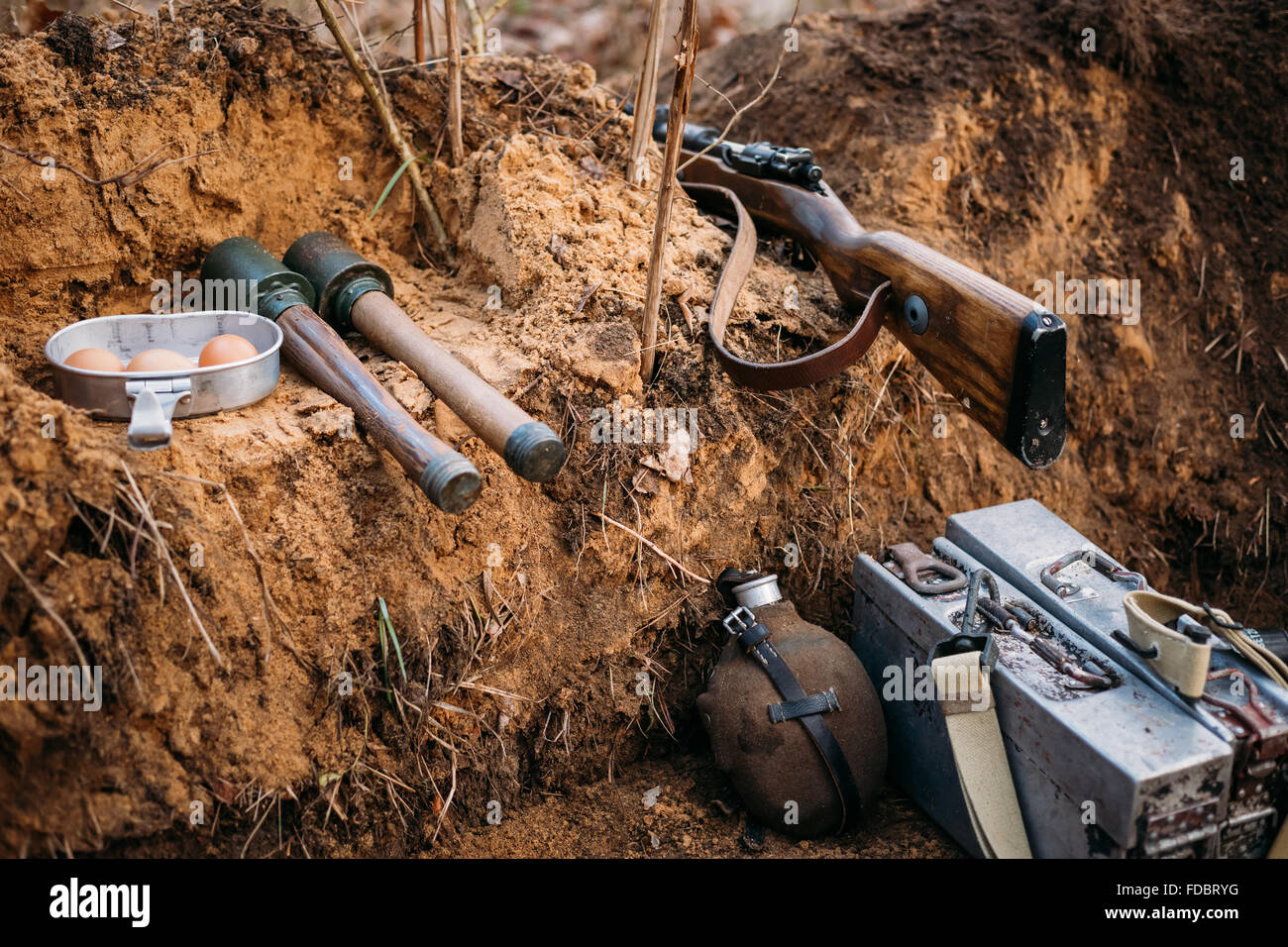 German military ammunition of World War II on ground. Rifle, grenades, flask. - Stock Image
