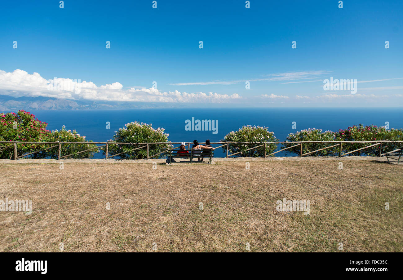 Three young women on a bench overlooking the Mediterranean Sea on the Gulf of Policastro on a lookout, Cilento,Campania,Italy Stock Photo