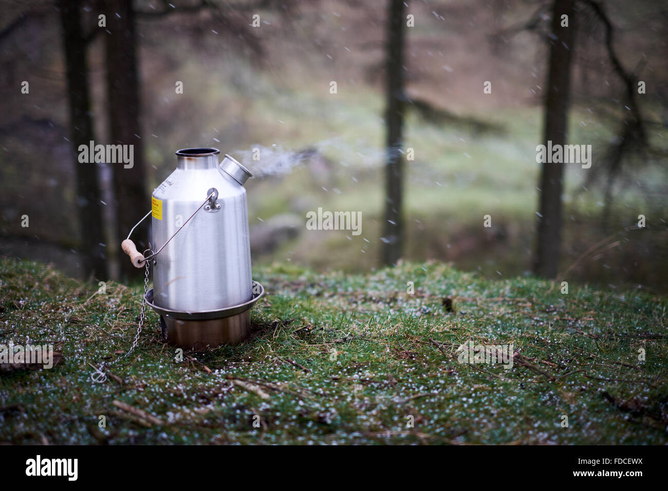A Kelly Kettle lit and burning with steam. Shot in the snow / hail / winter - Stock Image