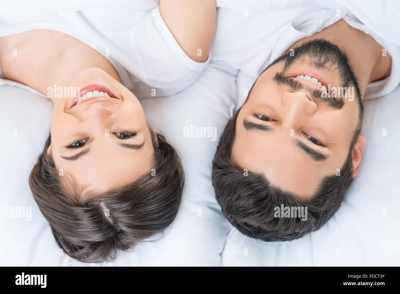 Nice loving couple lying in bed - Stock Image