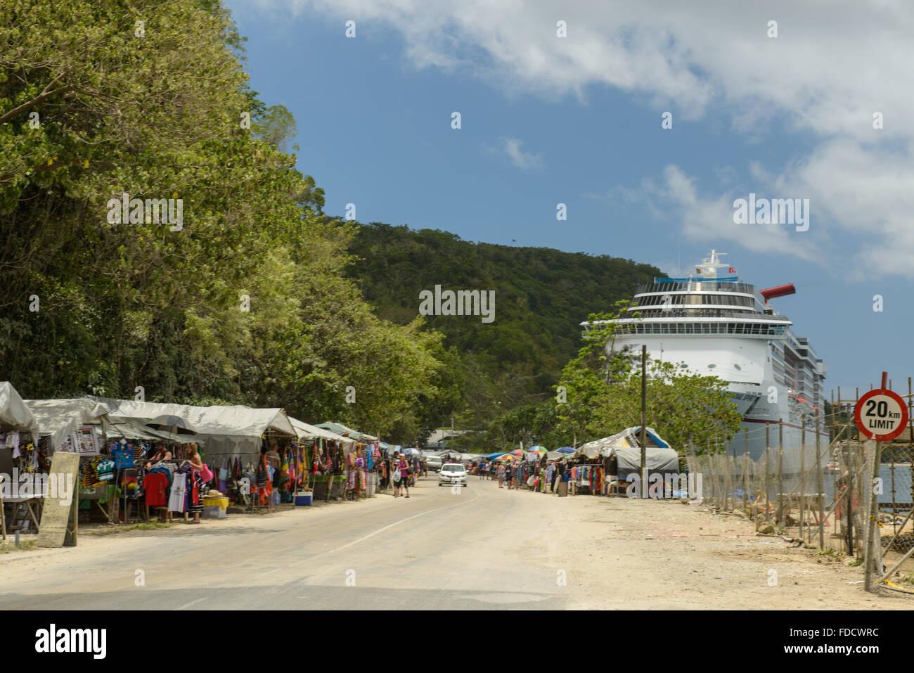 The cruise ship 'Carnival Spirit' docked at Port Vila, Vanuatu, dominates the quayside market. Stock Photo