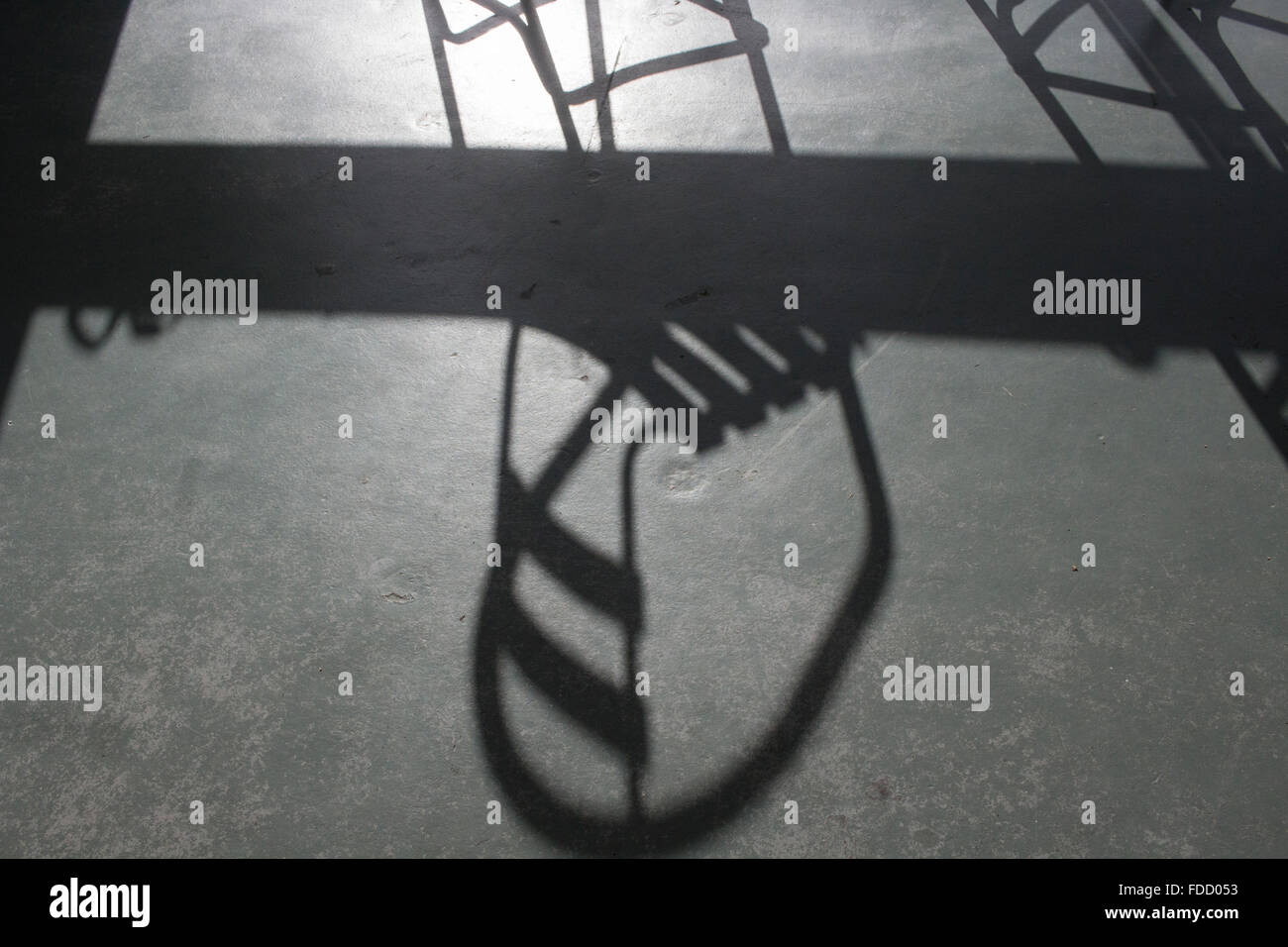 Chairs casting a shadow on a polished concrete floor Stock Photo