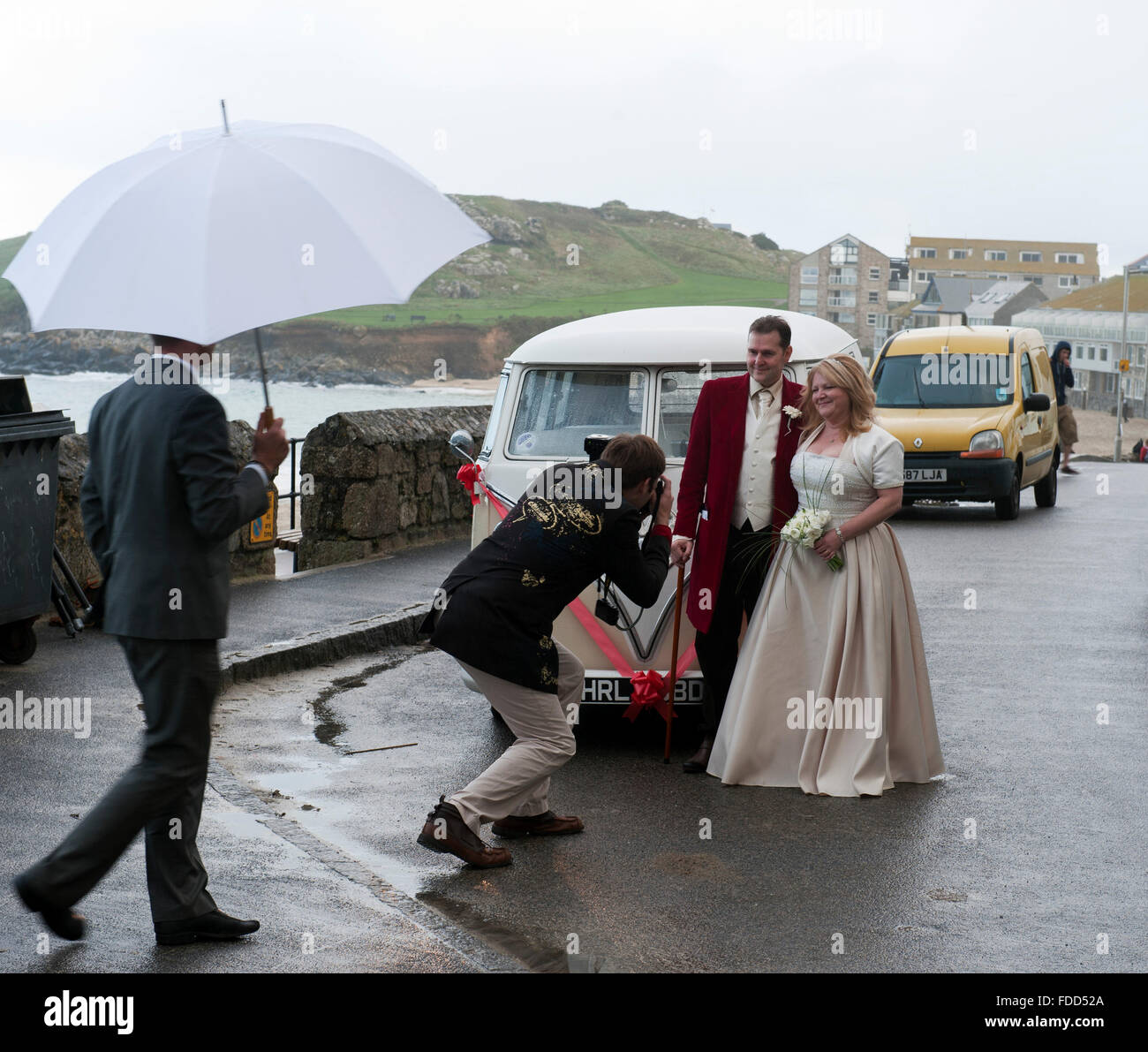 Bride and groom photographed in front of an Vintage Volkswagen VW Bus ca. 1965 oa a rainy day in St. Ives Cornwall - Stock Image