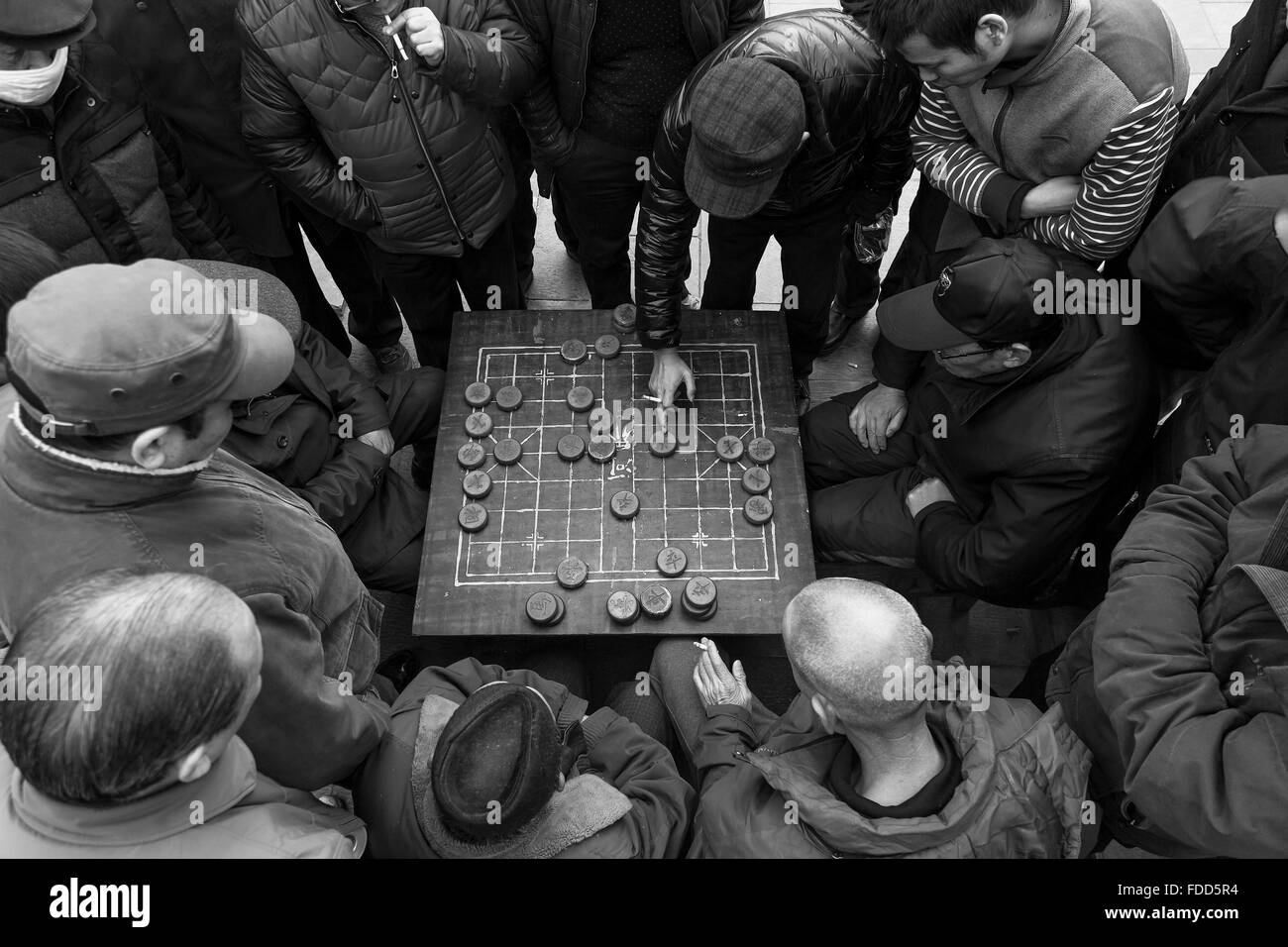 Chinese men playing Xiangqi at a park in a cold winter afternoon in Xi'an. - Stock Image