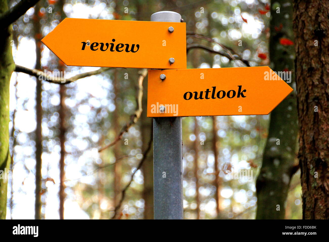 review and outlook written on a yellow direction sign - Stock Image
