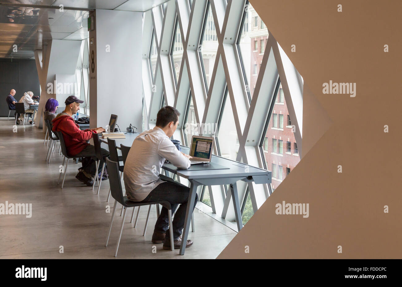 People working at desks and using computers in the Seattle Central Library, designed by Rem Koolhaas and Joshua - Stock Image