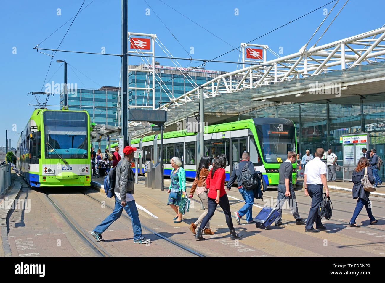People on pedestrian crossing tram tracks outside East Croydon train station public transport tramlink services - Stock Image