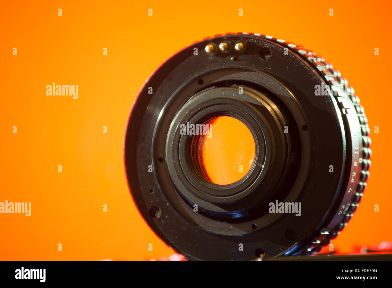 A lens on a orange background, viewed from the side of the mount. - Stock Image