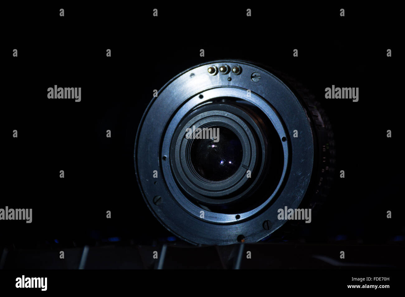A camera lens on a black background viewed from the side of the mount. - Stock Image