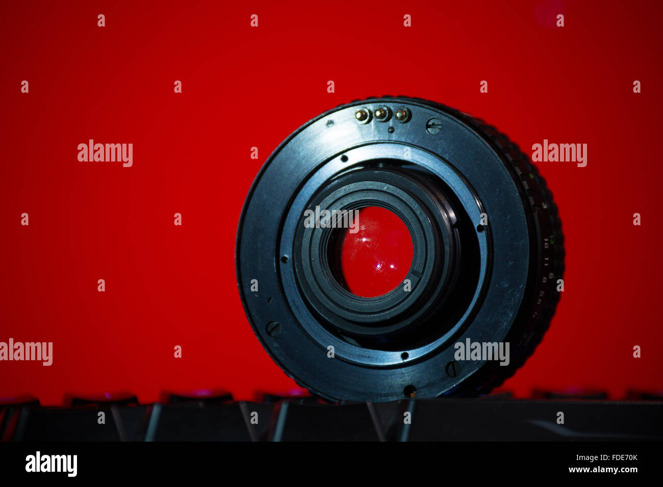 A lens from the side of the mount atop a keyboard in front of a red background. - Stock Image