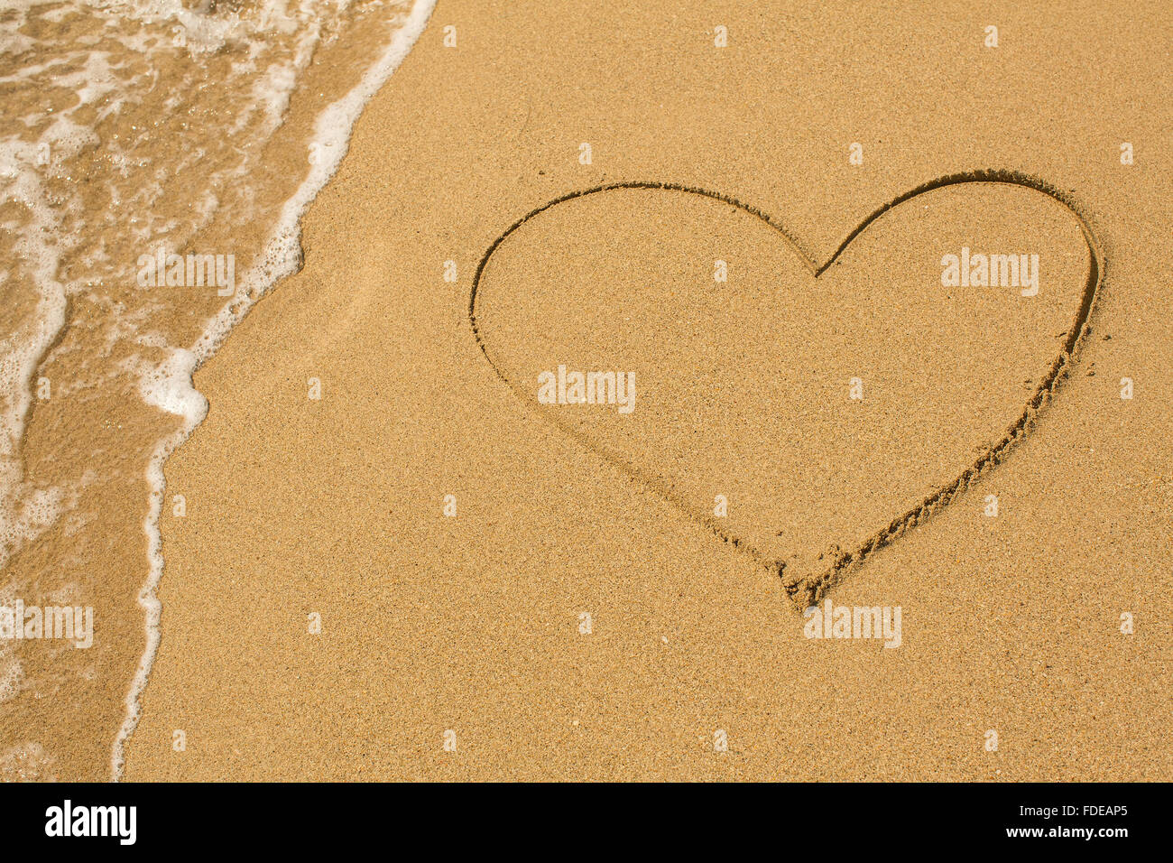 Heart drawn on the beach sand with a soft wave. - Stock Image