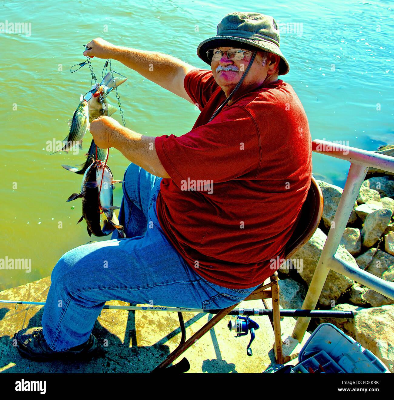 Burlington, Kansas, USA, 25th September, 2014 Lyndon a local fisherman shows off today's catch. A couple of - Stock Image