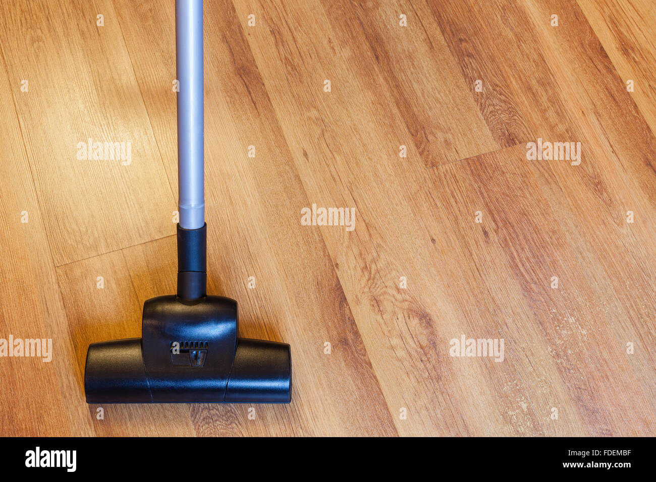 Front View Of Vacuuming Laminate Floor By Vacuum Cleaner At Home