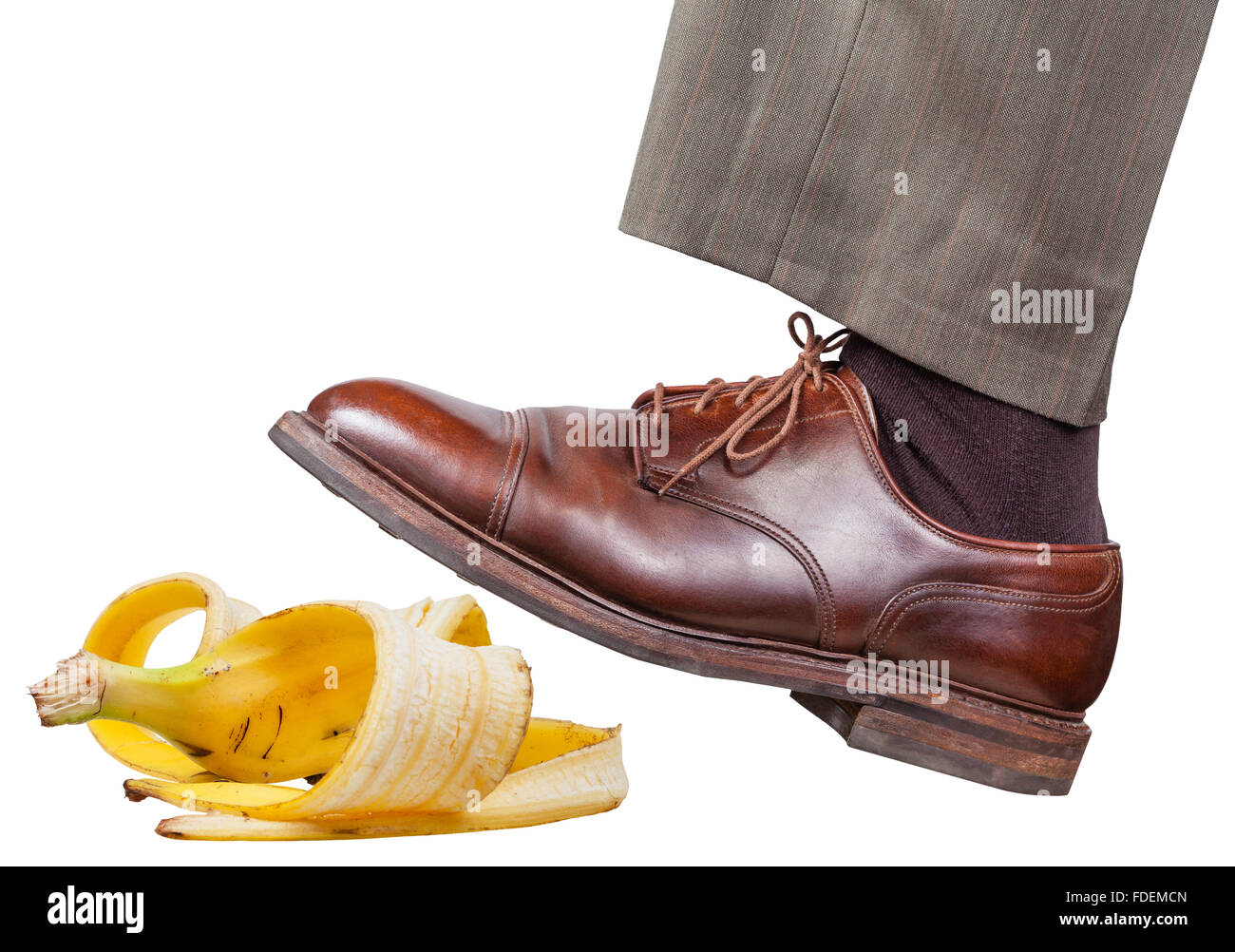 male leg in the left brown shoe slips on a banana peel isolated on white background Stock Photo
