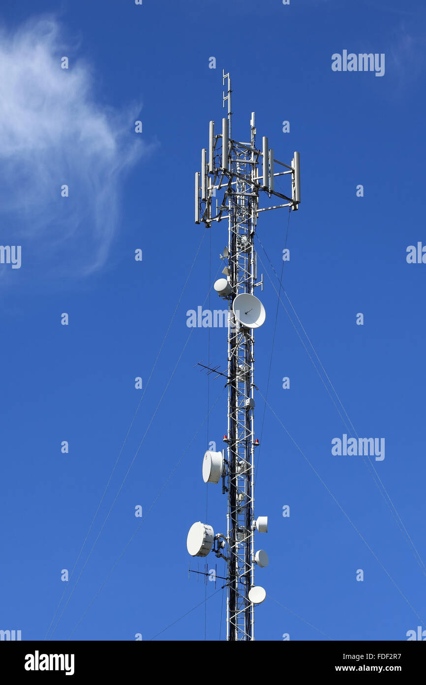 Antenna communications tower against clear blue sky. Stock Photo