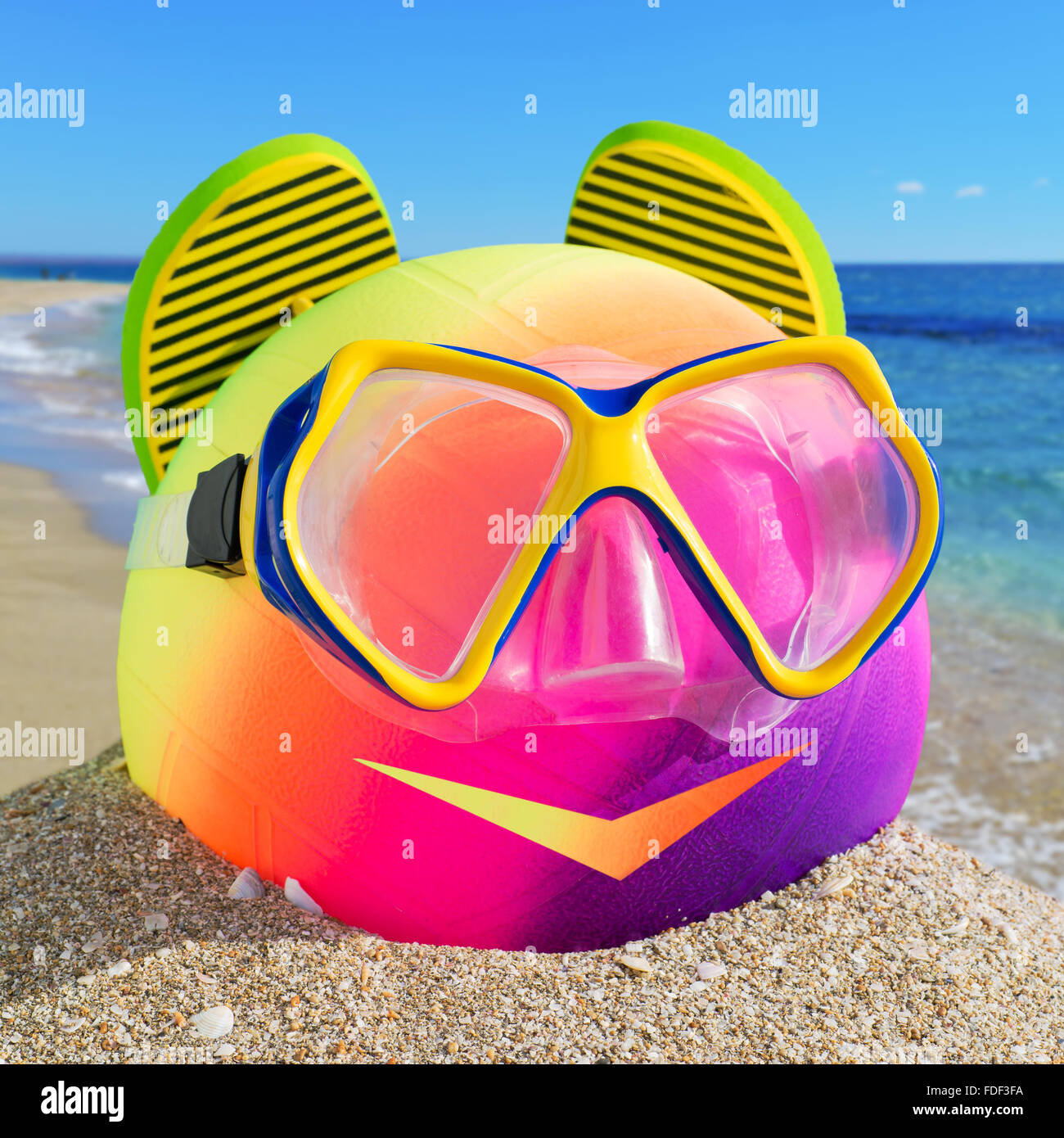 Smiling little man of beach accessories. Ball, flip-flop and diving mask on the beach against a blue sea and sky. - Stock Image