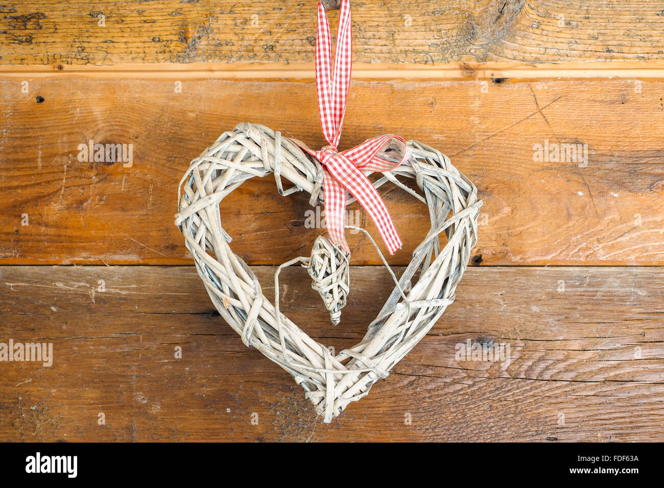 Home made heart built with straw, hanged to wooden wall to celebrate Saint Valentine day. - Stock Image