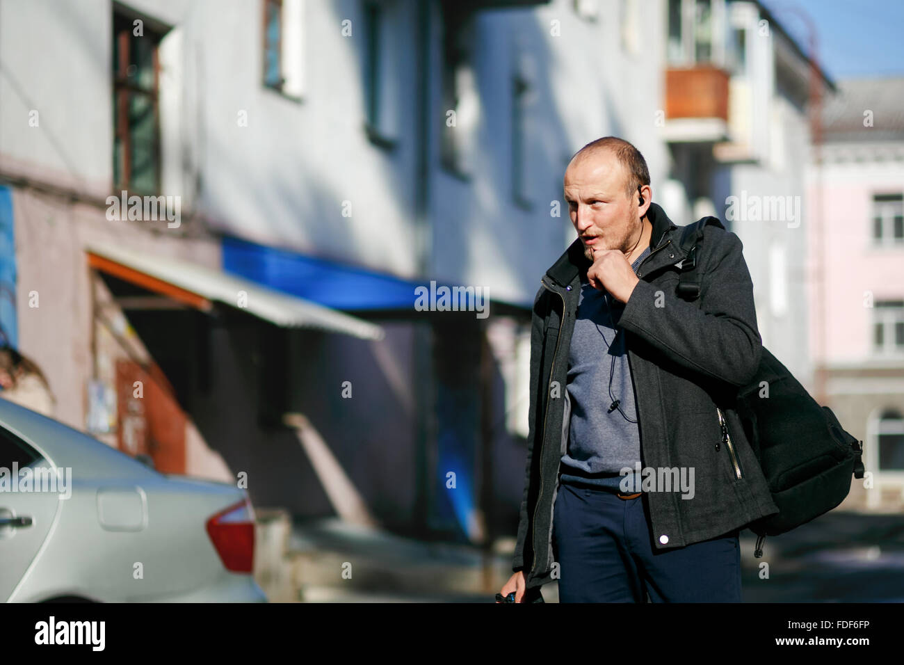 Brutal street photographer with camera in hand strolling city streets, talking on a walkie-talkie handsfree. - Stock Image