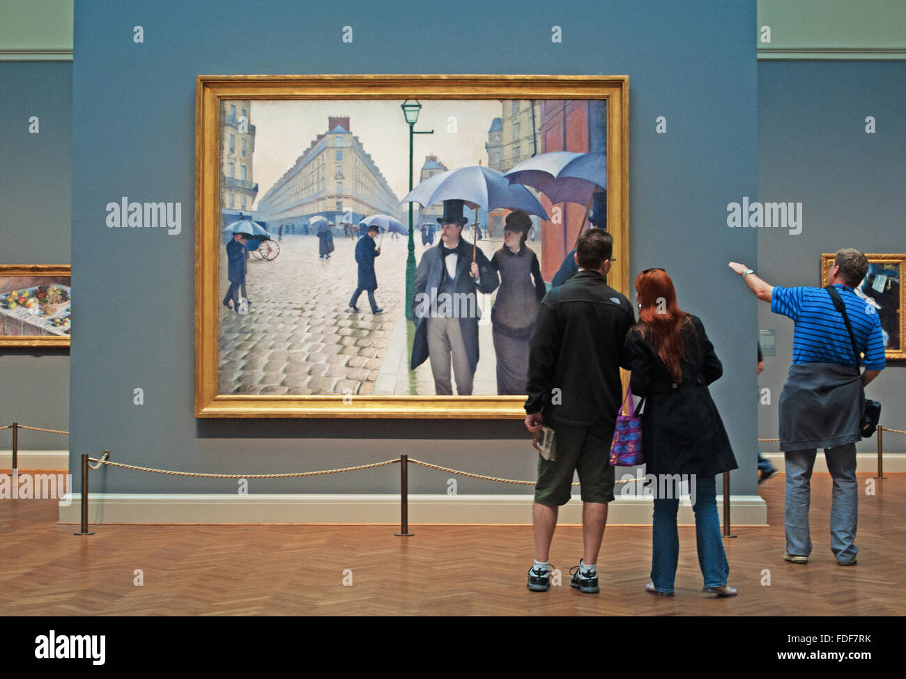 Chicago, Illinois, Usa: looking at the oil painting Paris Street Rainy Day by the artist Gustave Caillebotte in - Stock Image