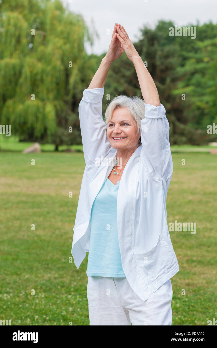 senior healthy old woman practicing yoga and tai chi outdoor - Stock Image