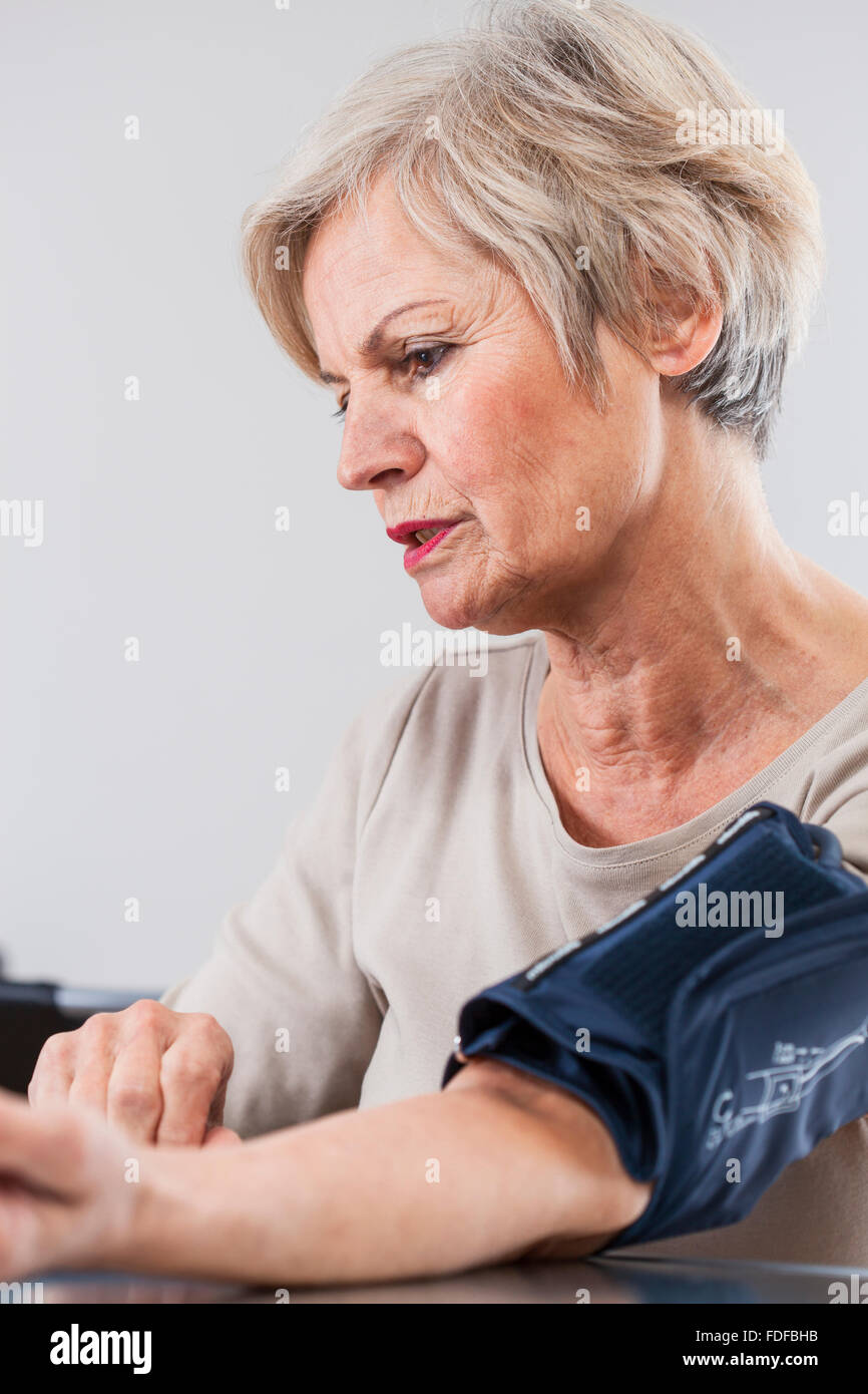 healthy happy smiling older senior woman checking blood pressure - Stock Image